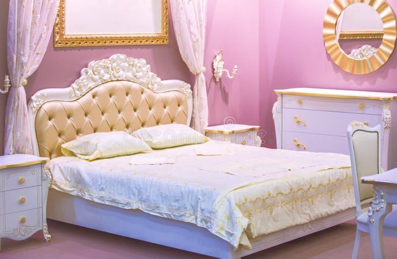 Camera da letto bianca e rosa di lusso nello stile antico con la decorazione ricca Interno di una camera da letto classica di sti fotografia stock
