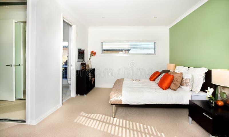 Camera da letto classica di una casa moderna con il letto bianco e molto cassetto nero e del cuscino e un'assicella fotografia stock