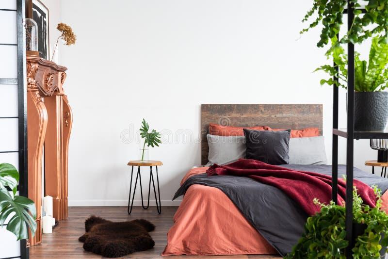 Camera da letto contemporanea con le lenzuola di corallo, il camino cuprico ed i lotti delle piante immagine stock libera da diritti