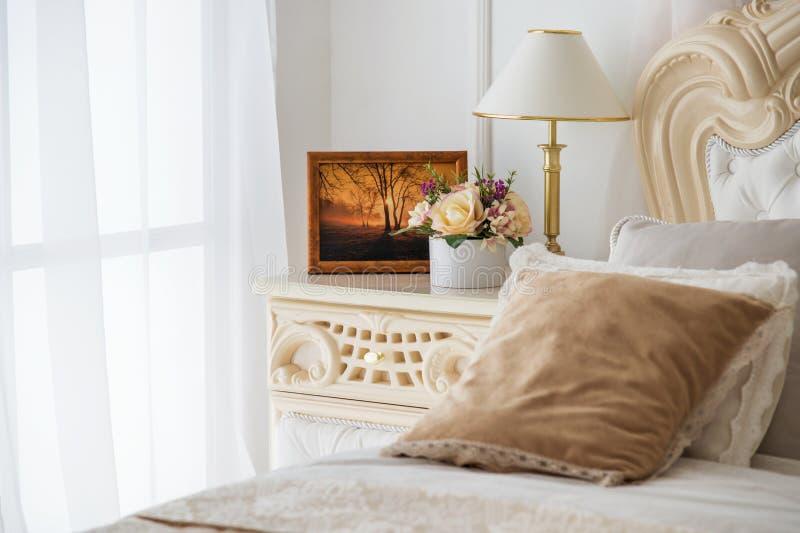Camera da letto d'annata bianca con la grande finestra immagini stock