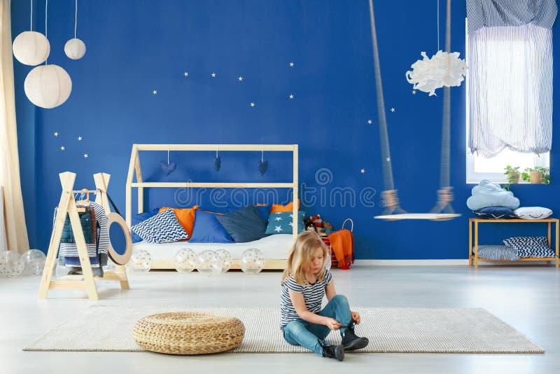 Camera da letto della ragazza con la parete blu immagine stock libera da diritti