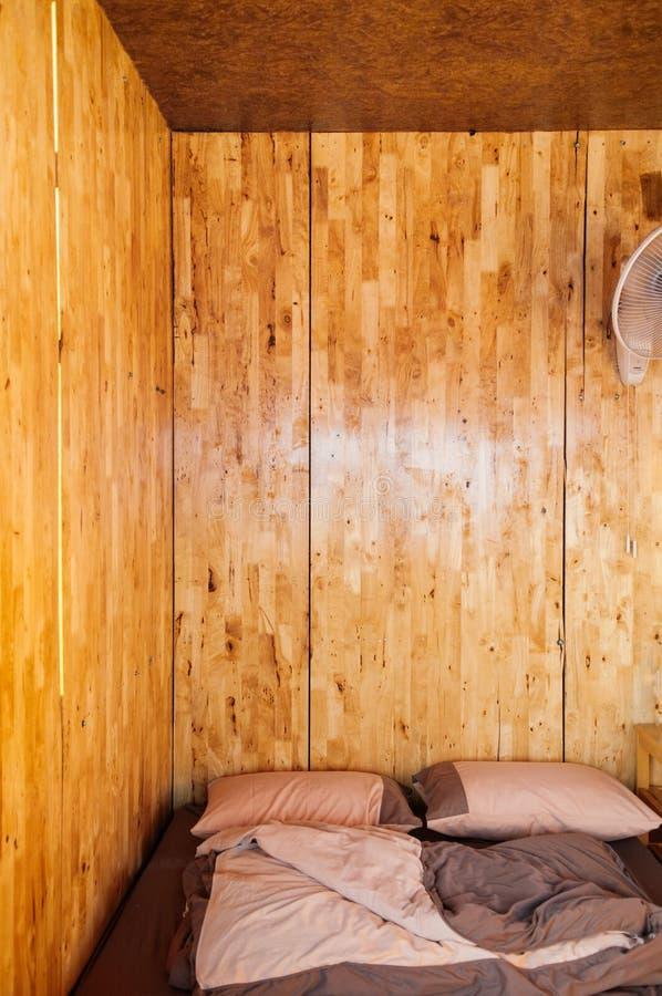 Camera da letto di legno accogliente calda della parete con il futon semplice sul pavimento, Lo immagini stock