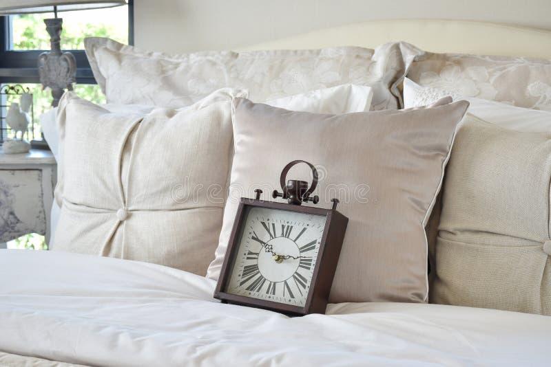 Camera da letto di lusso con la sveglia classica di stile sul letto fotografie stock