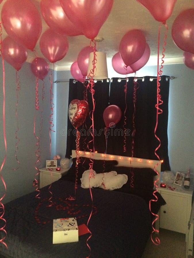 Camera da letto di San Valentino decorata con i palloni rossi dell'elio fotografia stock libera da diritti