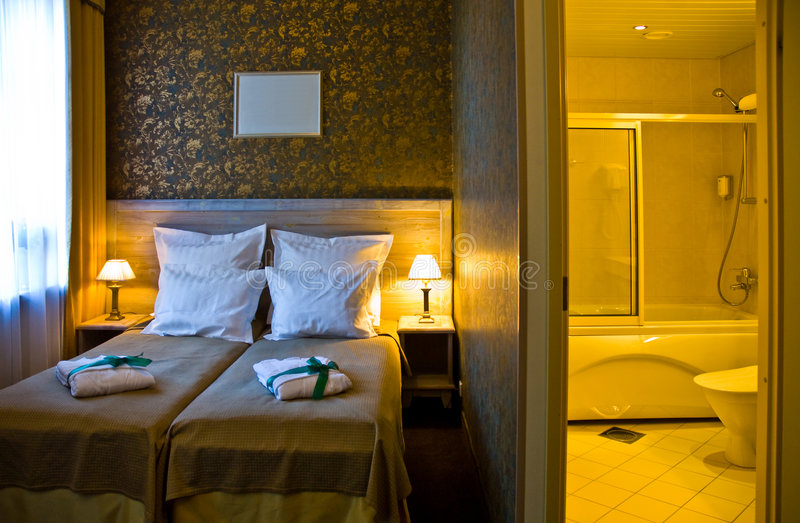 Camera da letto e stanza da bagno dell'hotel fotografie stock