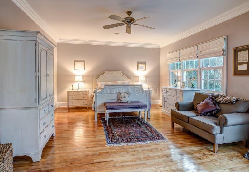 Camera da letto elegante con i pavimenti di legno e la mobilia raffinata fotografia stock libera da diritti