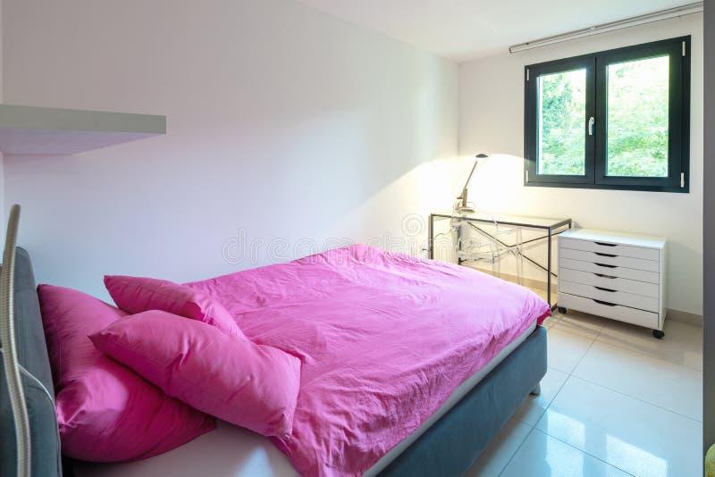 Camera da letto elegante con la finestra e copriletto o trapunta rosa fotografia stock libera da diritti