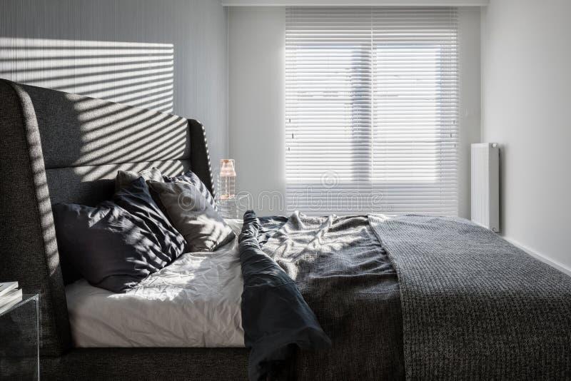 Camera da letto grigia con i ciechi di finestra fotografie stock