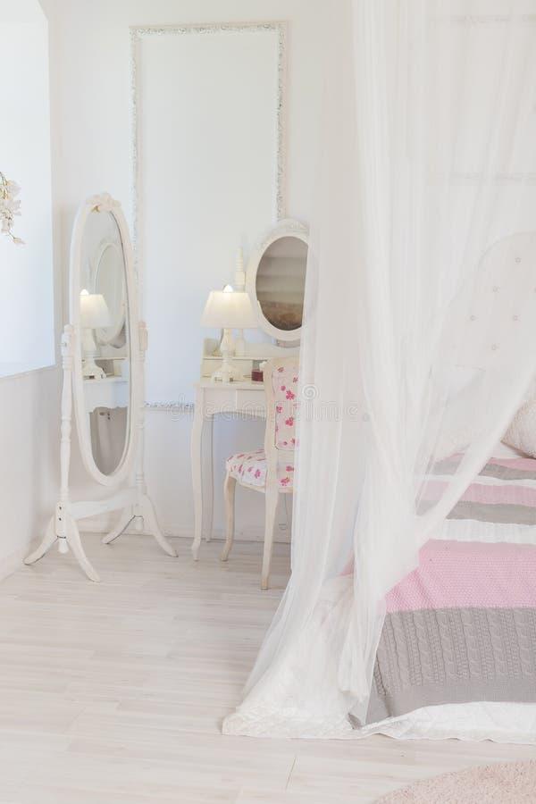 Camera da letto interna alla moda luminosa e pulita con una grande finestra panoramica bella mobilia antica ricca Letto a baldacc immagini stock libere da diritti