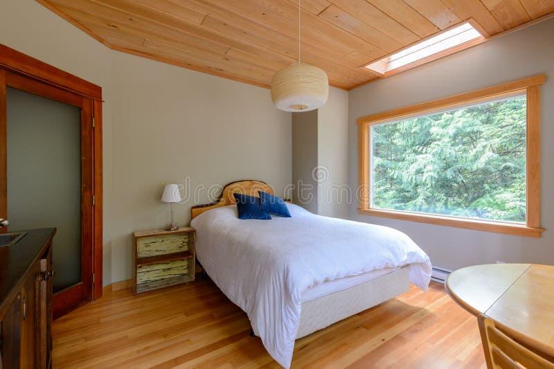 Camera da letto luminosa in un cottage rustico immagini stock
