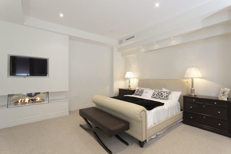 Camera da letto moderna con un camino immagini stock libere da diritti