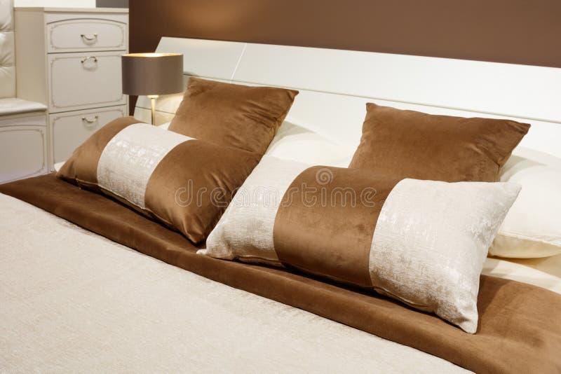 Camera da letto moderna di lusso di stile nei toni marroni e beige, interno di una camera da letto dell'hotel, cuscini con un orn fotografia stock