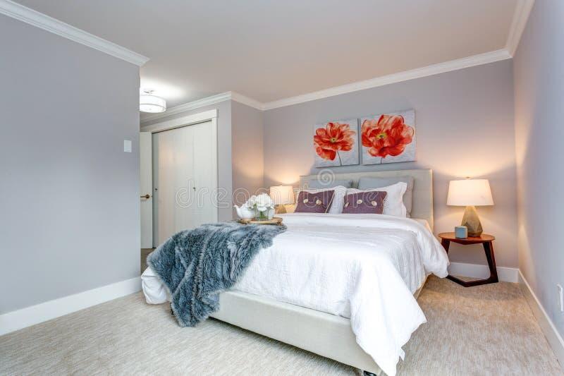 Camera da letto moderna leggera dell'appartamento con una vista del letto fotografie stock