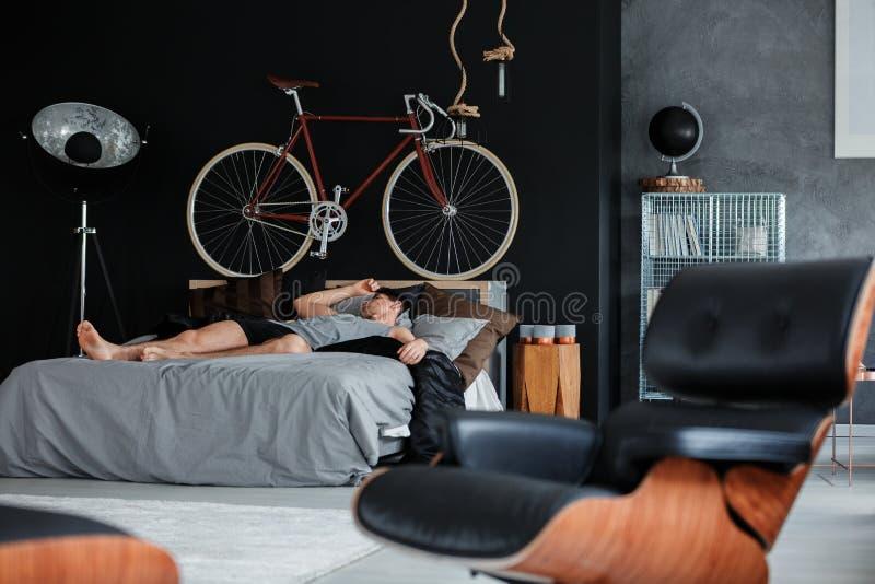Camera da letto monocromatica con l'uomo addormentato fotografia stock