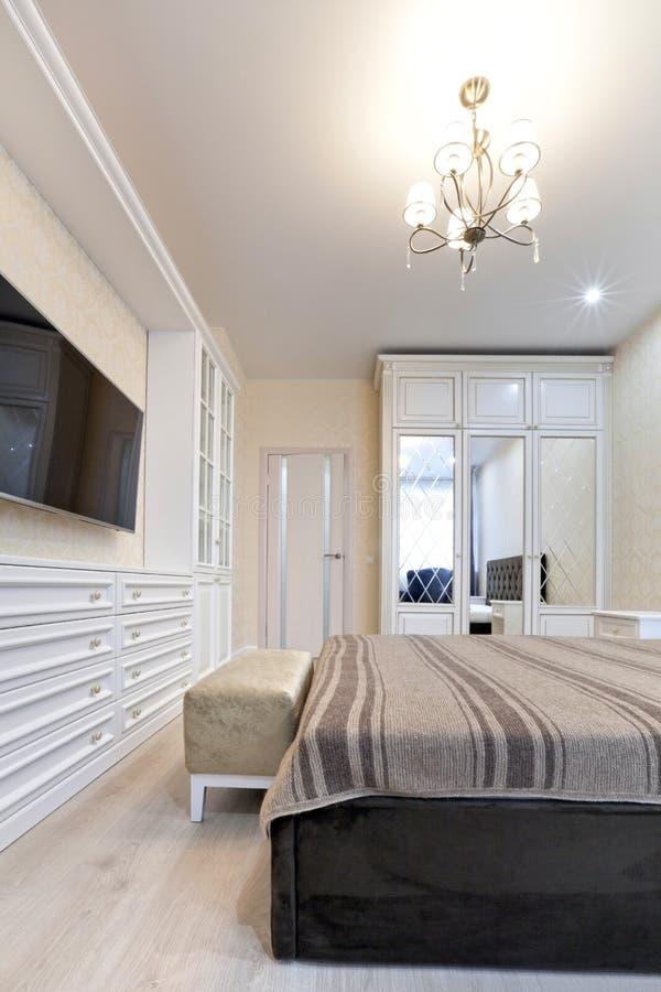 Camera da letto nei colori leggeri con mobilia di legno fotografie stock