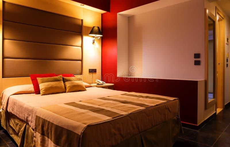 Camera da letto o camera di albergo moderna, calda, d'invito Luce ed ombre immagini stock