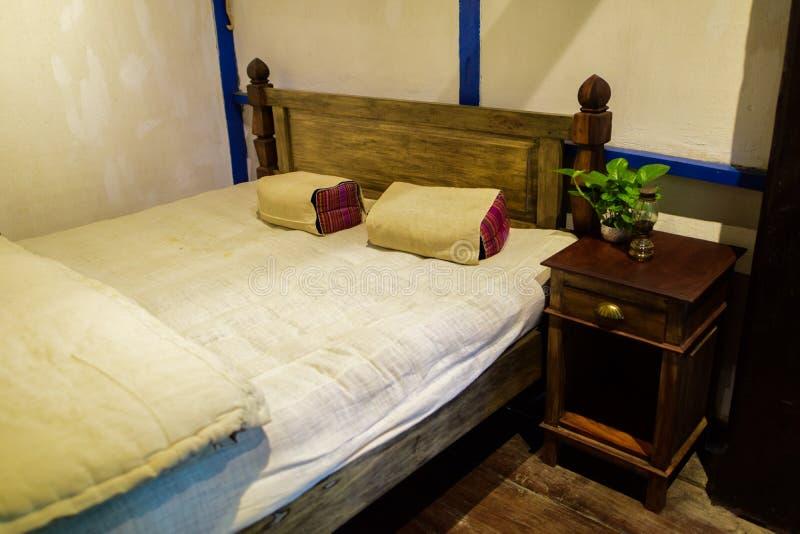 Camera da letto per due persone, il letto bianco ed i vasi di fiore fotografia stock