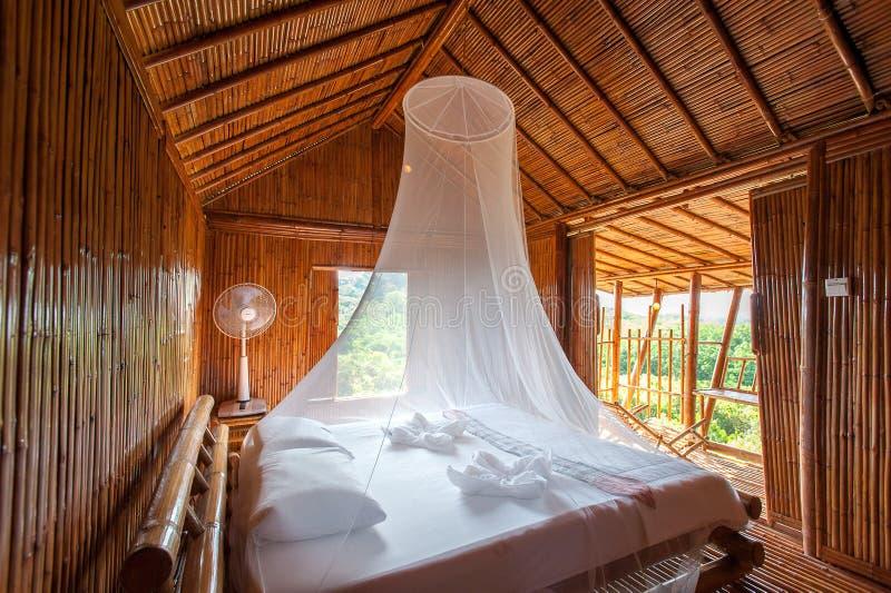 Camera da letto rurale di stile con il letto del baldacchino, bambù decorato Molto schiocco immagini stock libere da diritti