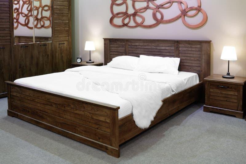 Camera da letto rustica moderna e di legno di lusso di stile nei toni marroni e beige, interno di una camera da letto dell'hotel fotografie stock