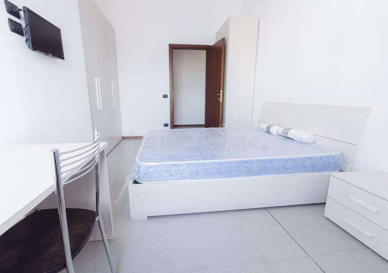 Camera da letto stile studente semplice del dormitorio con i lotti di luce fotografia stock libera da diritti