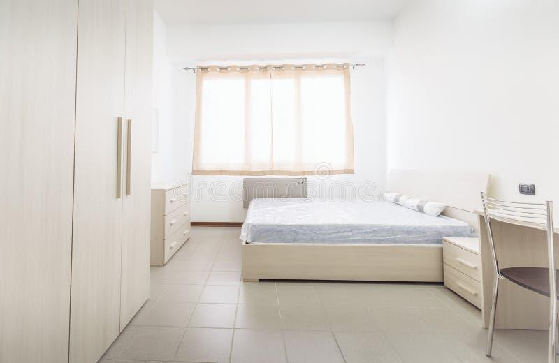 Camera da letto stile studente semplice del dormitorio con i lotti di luce fotografie stock