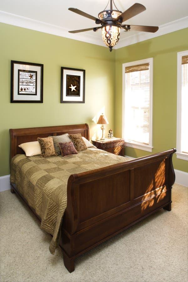 Camera da letto verde con il ventilatore di soffitto fotografia stock libera da diritti