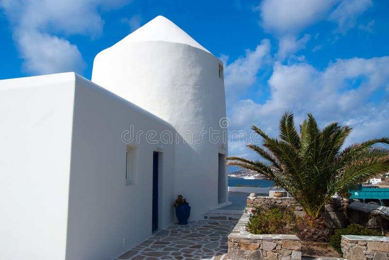 Camera dal mare in Mykonos, Grecia Costruzione e palma imbiancate su cielo blu soleggiato Architettura e progettazione tipiche de fotografia stock libera da diritti