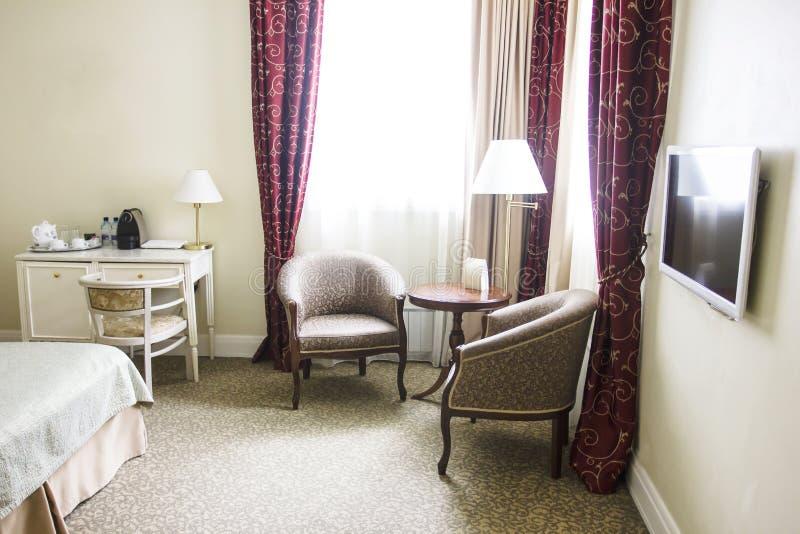 Camera di albergo nei colori, nell'area di seduta, in poltrone ed in finestra calmi fotografia stock libera da diritti