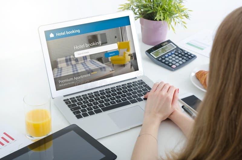 Camera di albergo di prenotazione della persona sul computer portatile immagine stock libera da diritti