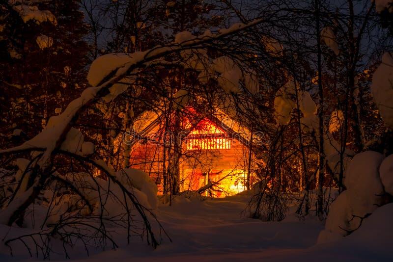 Camera di legno accesa nella foresta di inverno di notte fotografia stock