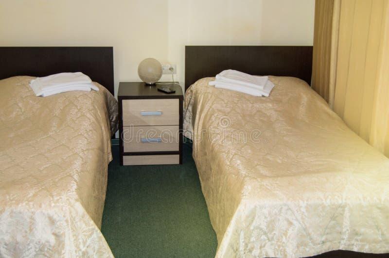 Camera doppia moderna con due letti singoli, comodino, asciugamani e lampade da tavolo, stanza economica accogliente per i viaggi immagine stock