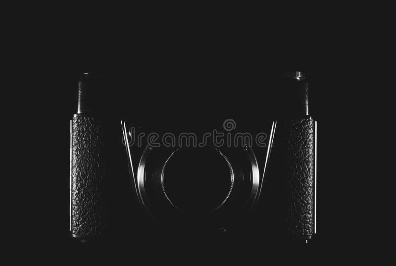 A camera enlightened only by sides on a black background. An old camera enlightened only by sides on a black background, in black and white royalty free stock photos