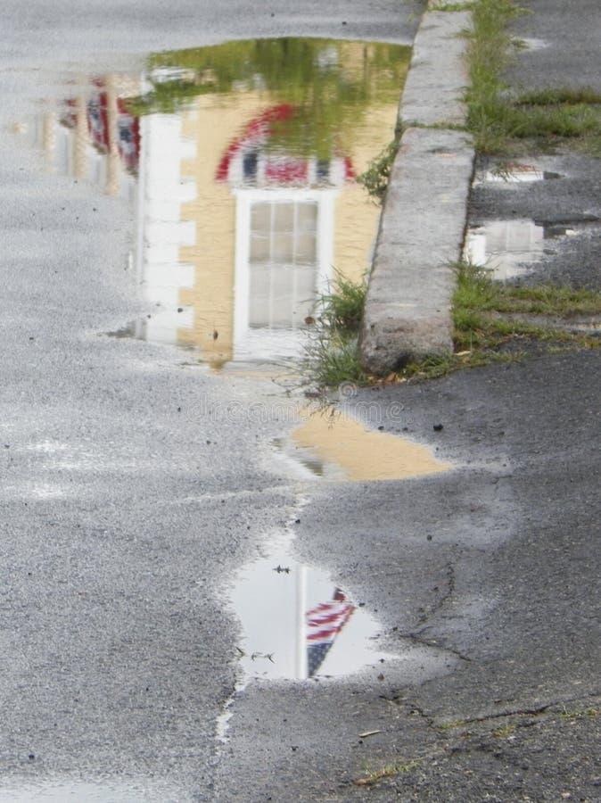 Camera gialla con la bandiera americana riflessa in pozza fotografia stock