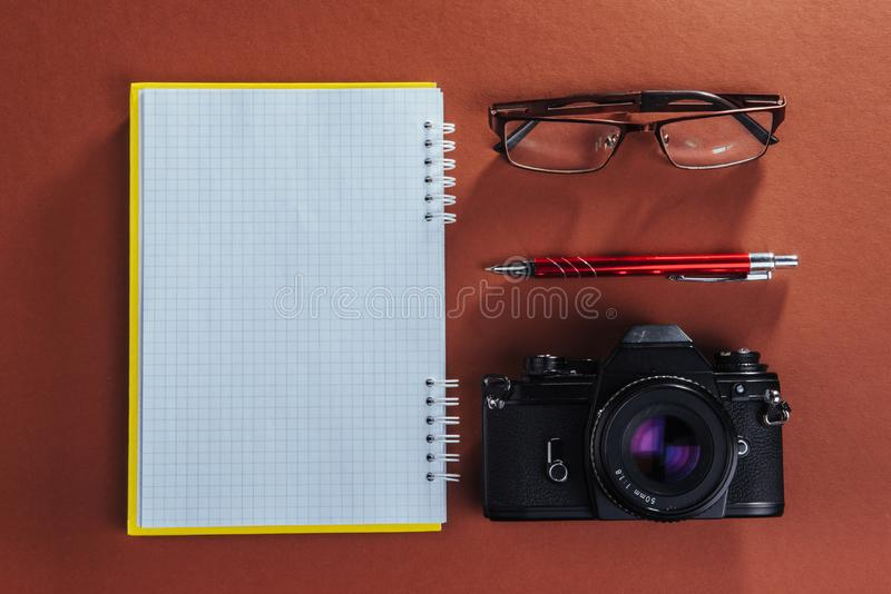 camera, glasses and notepad and pencil on a brown wooden background royalty free stock photography
