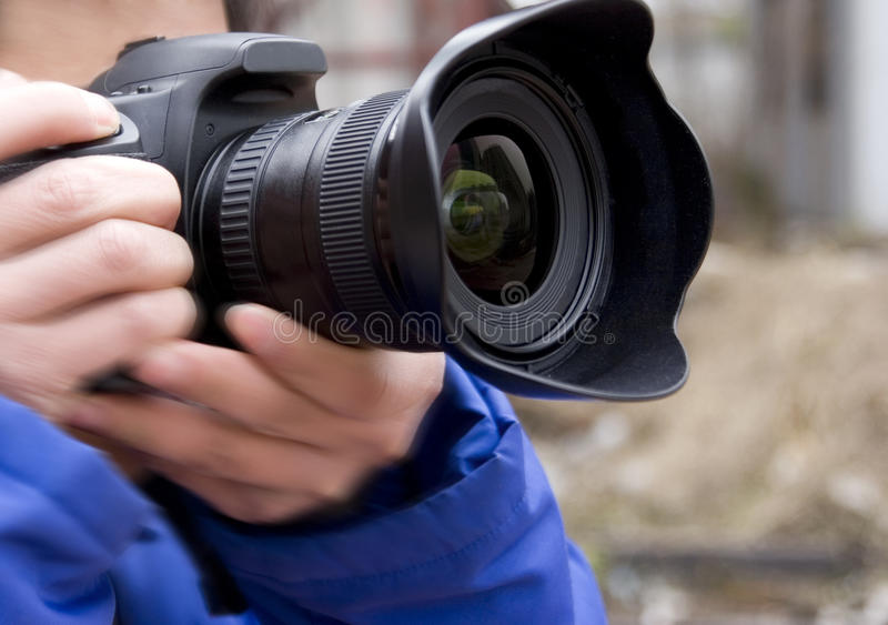 Camera in hand. A photographer is holding a camera shooting photos stock images