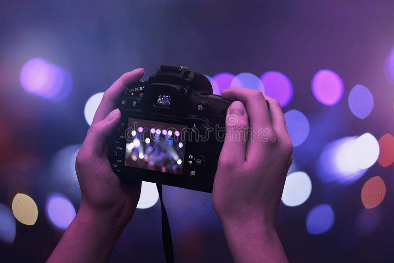 Camera in hands. Bokeh and concert, live music lights in background.  stock photography