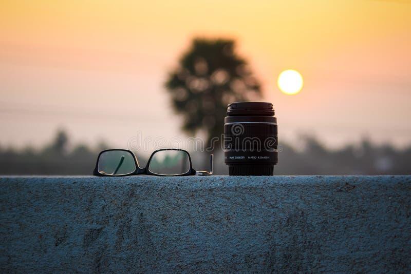 Camera lens and eyeglasses at sunset royalty free stock photo