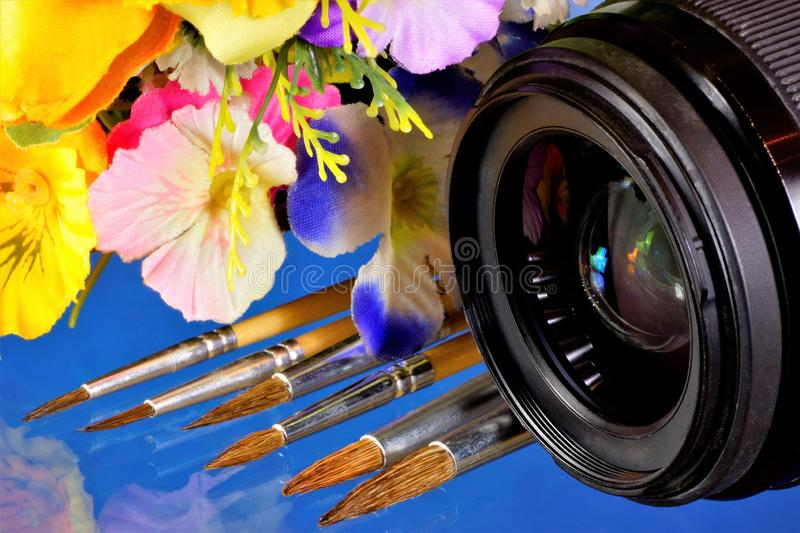 Camera lens, summer flowers and artist`s brushes. The lens is an optical device for creating an optical image. Garden summer stock photo
