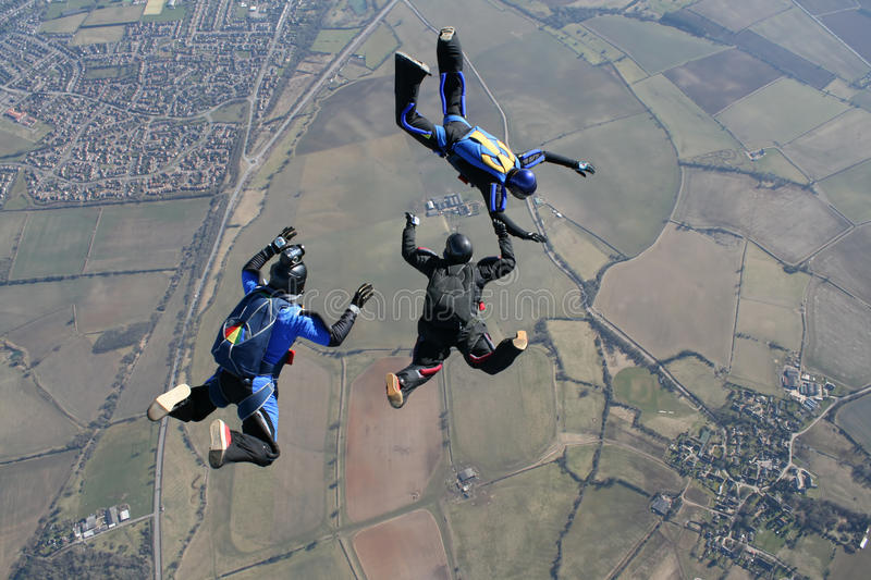 Camera man filming to skydivers stock image