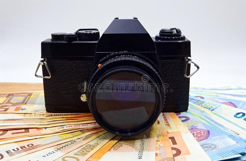 Camera and money on wooden table. Concept for microstock photography. Studio shot stock image