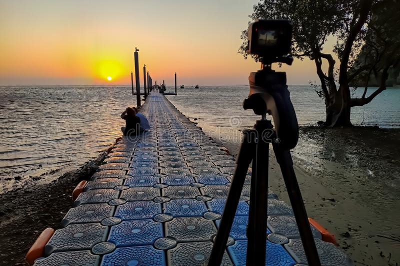 Camera mounted on a tripod shooting a coupe on the pier and sunrise under the sea. Focus on man and woman royalty free stock image