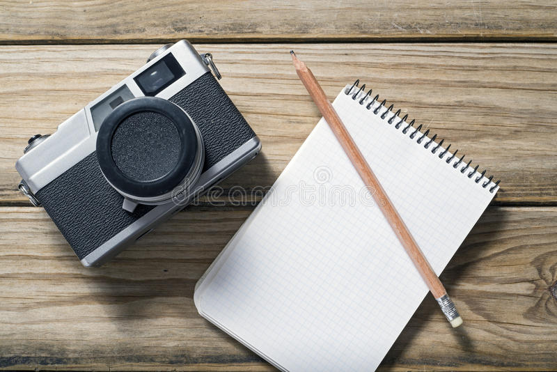 Camera and notebook. Analog photographic camera and notebook over wooden surface stock images