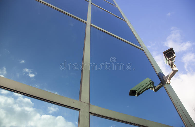 Camera on office building reflecting clouds royalty free stock photos