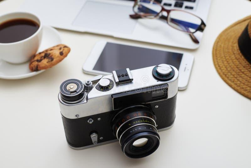 Camera op de voorgrond en de gadgets, oogglazen, hoed en een kop stock foto's