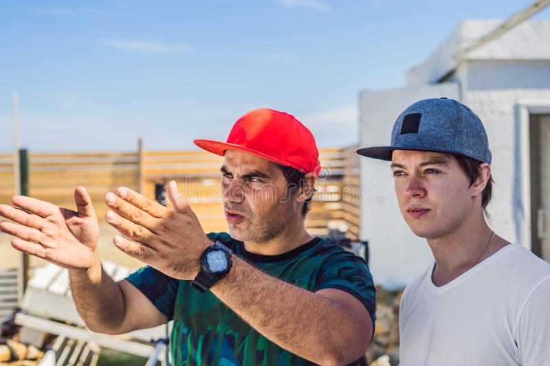 Camera operator and director discuss the process of a commercial video shoot.  stock images