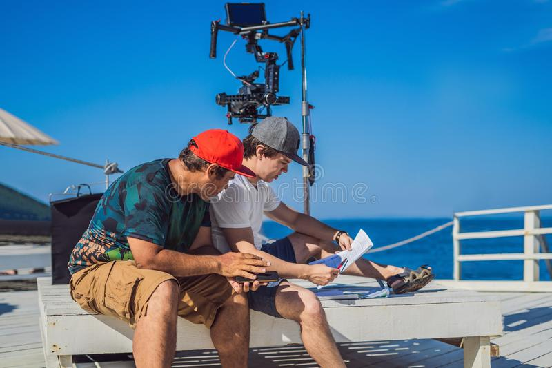 Camera operator and director discuss the process of a commercial video shoot.  stock photography