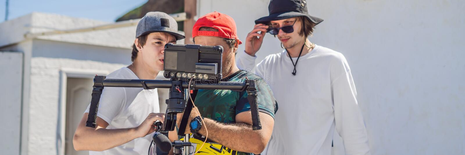 Camera operator, director and dp discuss the process of a commercial video shoot BANNER, LONG FORMAT. Camera operator, director and dp discuss the process of a stock images