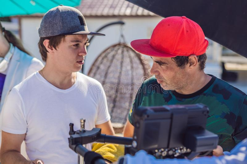 Camera operator, director of photography and director discuss the process of a commercial video shoot.  royalty free stock images