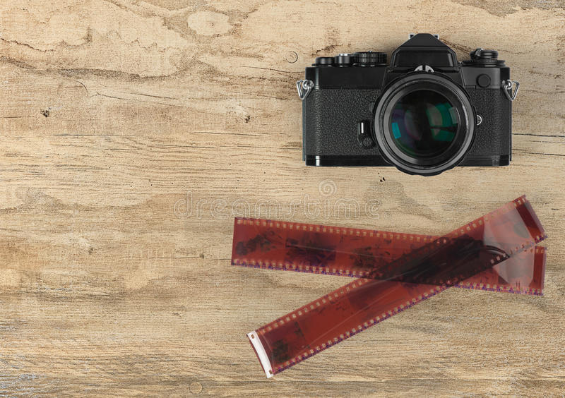 Camera and photographic 35 mm film strip on wood. En background stock photo