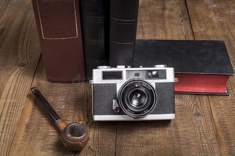 Camera and Pipe. Old Camera Closeup on old Books and Brown Wood Background stock photography